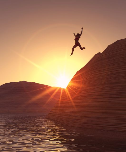 A woman jumping from a cliff in to the water.