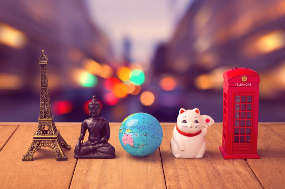 Travel around the world concept. Souvenirs from around the world on wooden table over city bokeh background