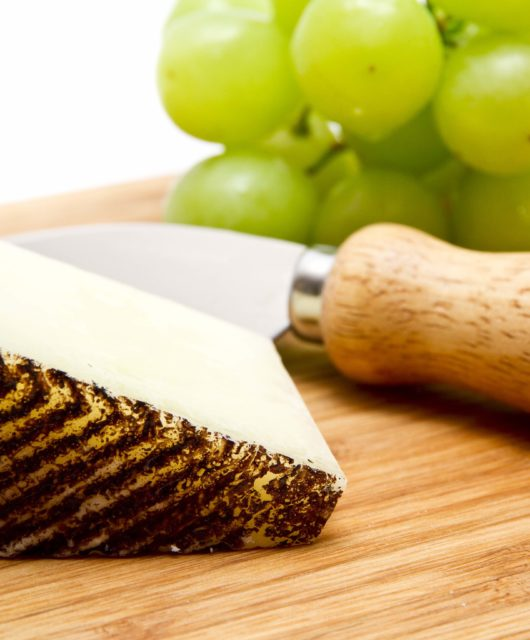 Manchego cheese and green grapes on chopping board