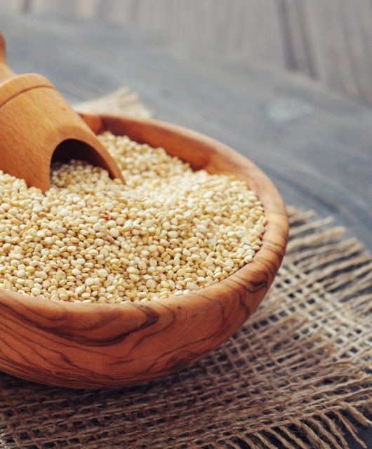 Raw quinoa seeds in the wooden bowl on wooden background closeup