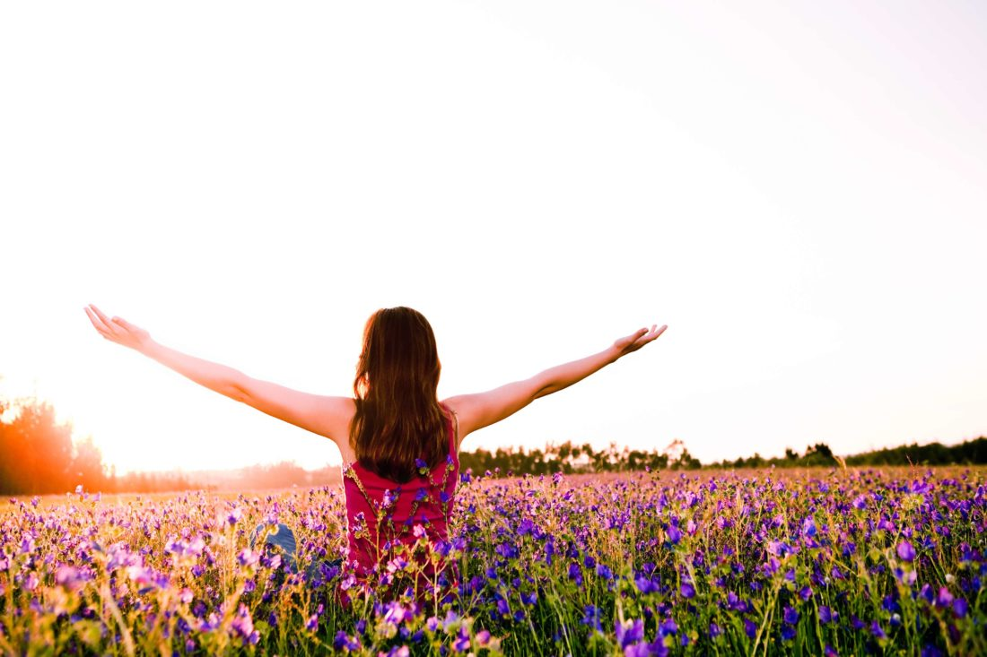 Free girl enjoying the nature on a beautiful flowery field